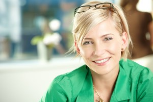 Closeup portrait of attractive young businesswoman wearing green