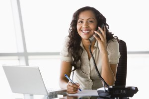 Middle Eastern Business Woman At Desk Using Phone And Laptop