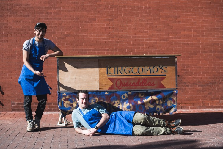 two guys in front of a brick wall with a quesadilla food cart and blue aprons