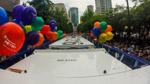 VIew of pride parade from atop a bus, with balloons