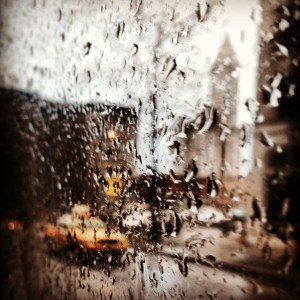 Looking out a window through raindrops on a Metro bus.