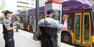 King County Metro fare enforcement officers on Third Avenue, waving to passing trolleybus