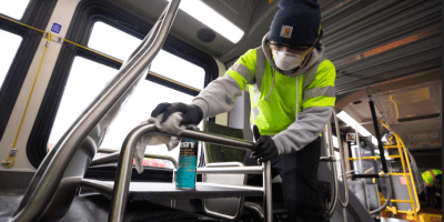 Tyler Goodwin cleans the interior of a bus with a rag and cleaner wearing protective mask and goggles