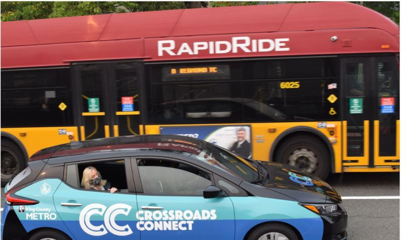 Crossroads Connect vehicle drives to the side of RapidRide bus with masked passenger looking through rolled down window.