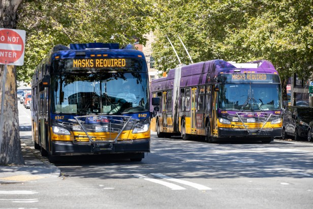 "Two Metro buses downtown. Their destination signs read ""Masks required."""