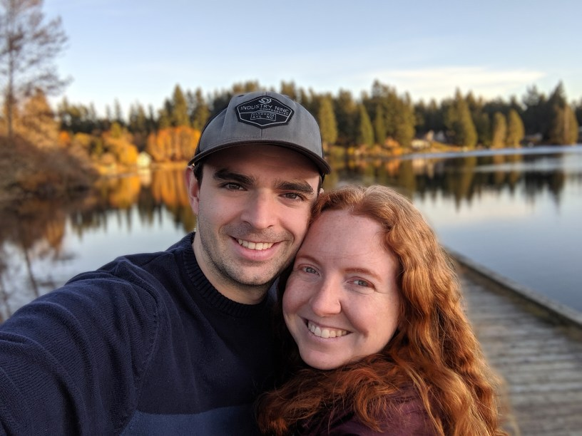 Aaron and Elina pose together in front of a lake