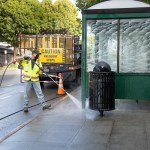 Facilities staff cleaning a bus shelter
