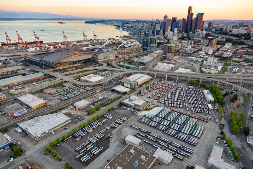 aerial photo of Metro bus base in Seattle in the foreground and with the skyline, Elliott Bay and port in the background