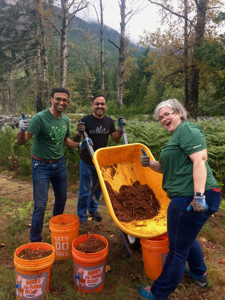 Adult volunteers with a wheelbarrow of mulch at Tanner Landing Park.