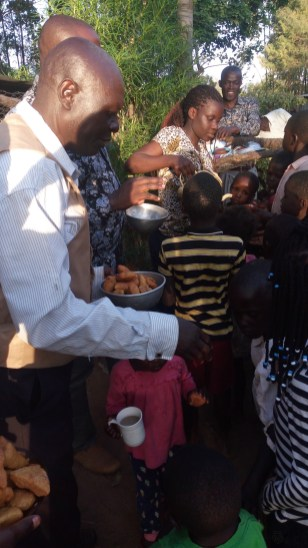 Pastor Moses and the team serving orphans with tea and Mandasi its called bun cakes in your country