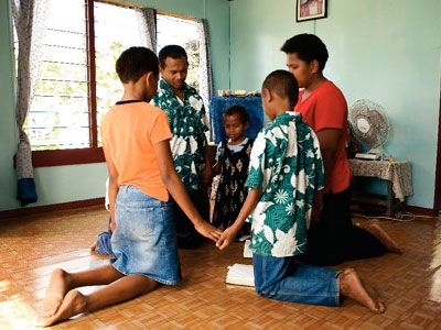 Family on their kneels forming a circle with helped hand praying_in the post_developing your Devotional Life by Peter Tan