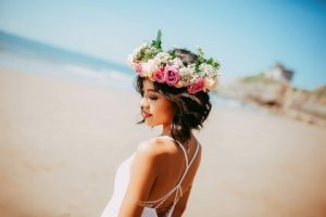 Picture of a woman on a beach with a wreath of flowers on her head looking serene