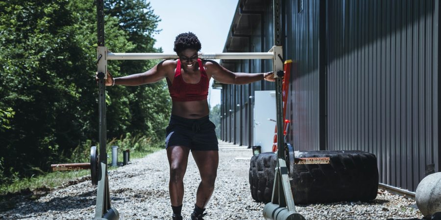 black woman carrying weights depicting mentally strong