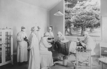 Surgeons wearing white robe-like uniforms, caps, and face masks operating in a simple white room.