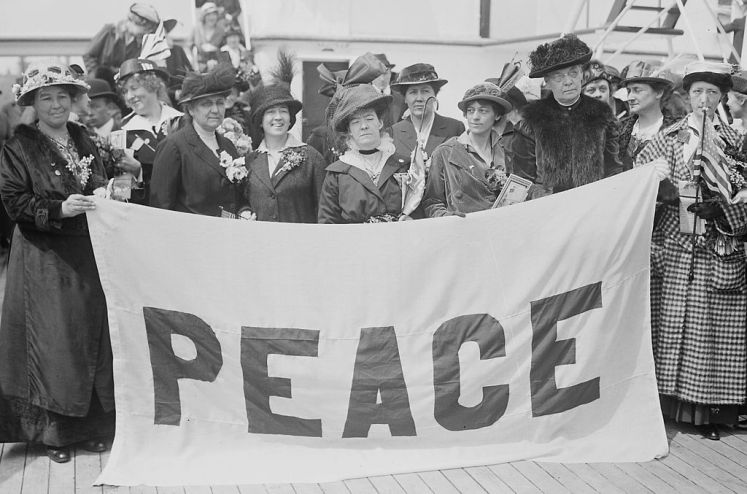 """Delegates to the April 1915 Women's International Congress for Peace and Freedom aboard the MS Noordam with their blue and white """"PEACE"""" banner"""