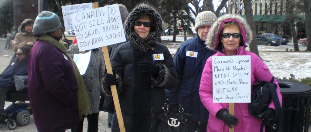 """Two seemingly-retirement age women holding signs which read: """" CANADA DO NOT SELL ARMS TO SAUDI ARABIA. STOP ARMS SALES!"""" and """"Canada, spend more on people's NEEDS - LESS on WAR - Make pace NOT WAR. Regina Peace Council."""""""