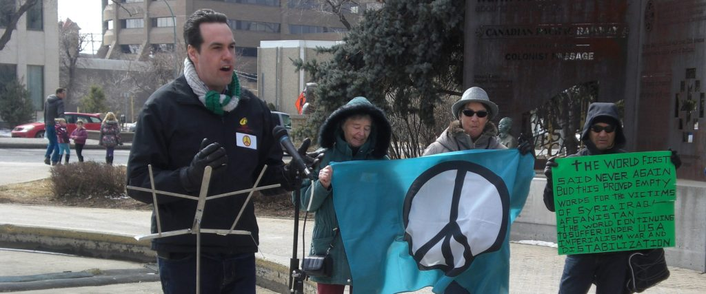 MP Erin Weir speaking to the crowd with 3 participants holding a peace flag and demonstration sign in the background