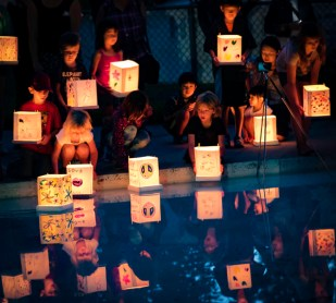 shows about eleven children lit by the glow of their paper lanterns floating in a pool.