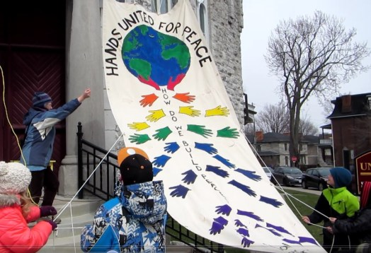 Margaret Moncreif and students raising the Hands United for Peace Banner on a chilly day in April 2016.