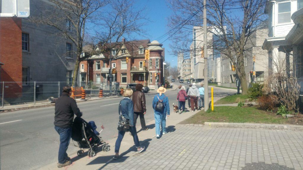 Ten people with their backs to the camera walking up a stretch of Johnson Street between stops 3 and 4 on the tour.