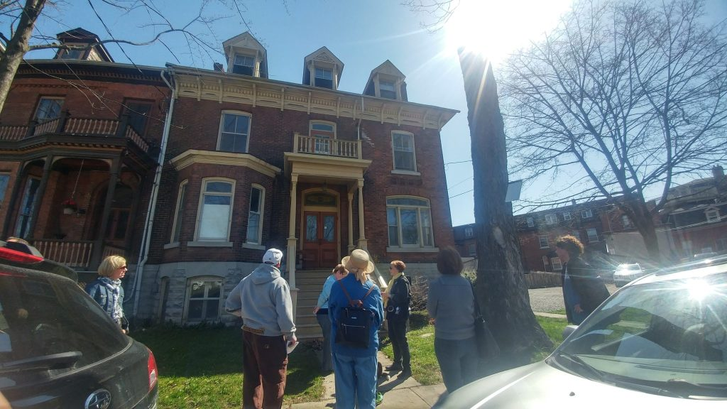 Six individuals are visible in the foreground staring up at a 2.5 story brick heritage house at 55 West Street at Stop 4A on the tour.