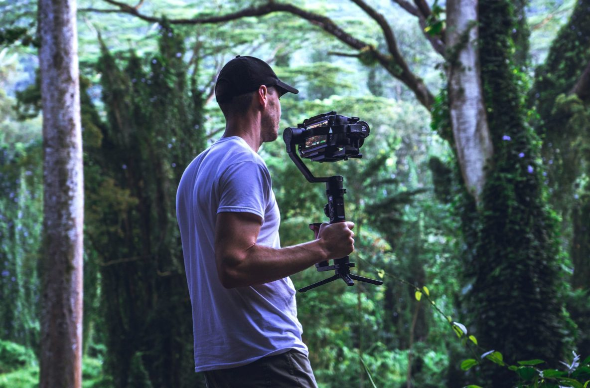 man with video and gimbal in wood jungle