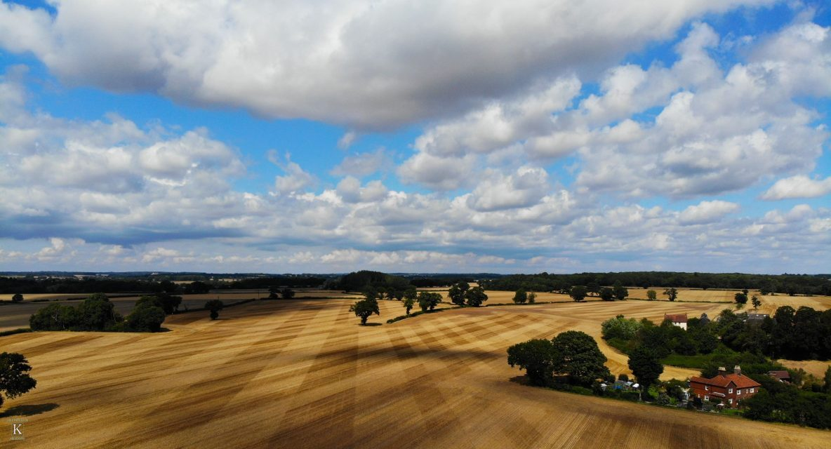Drone shot of countryside with fields and clouds