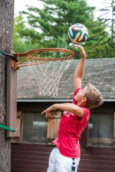 boy playing field basketball at summer camp