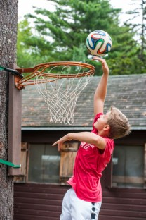 boy playing field basketball at summer camp
