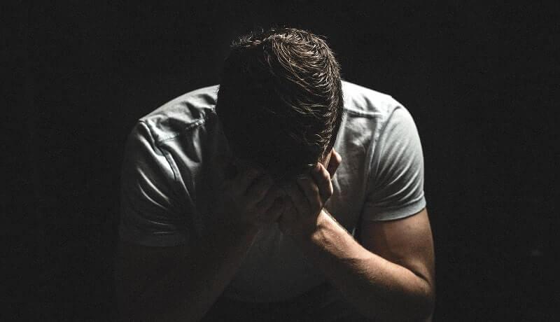 暗闇の中で顔を隠す男の画像