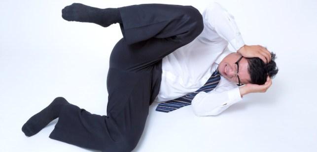 倒れて頭を抱えるスーツの男性