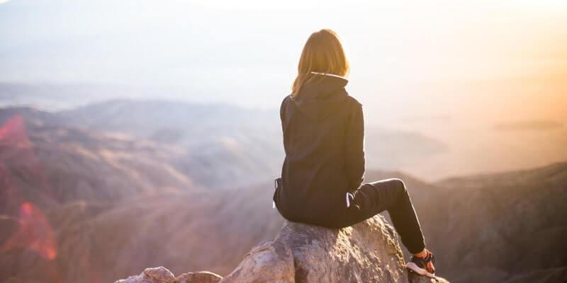 山頂に座って景色を眺める女性