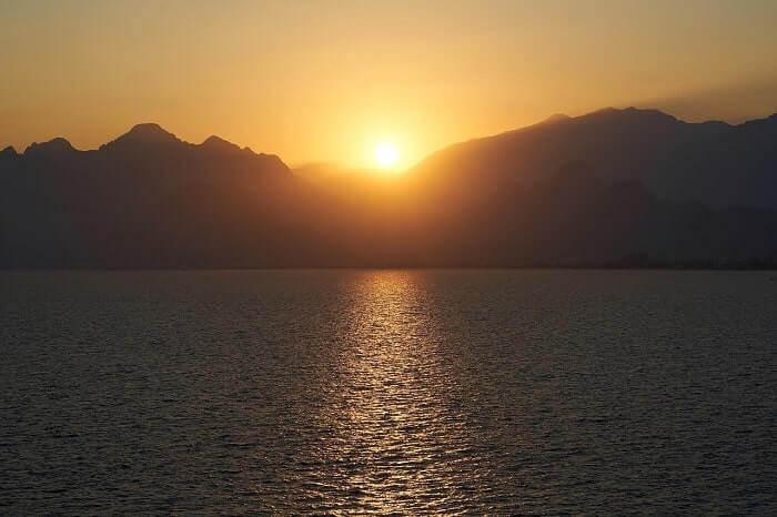 湖から見える山岳に沈む夕日