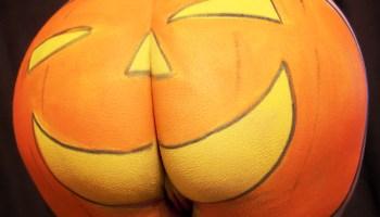pumpkin face paints onto womans bottom for Halloween