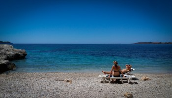 couple sitting alone together on the beach with beautiful blue sea water