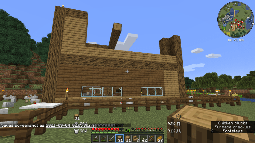 The side of the house, you can see more progress on the top, with some ceiling beams of logs visible.