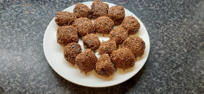 A white plate with homemade chocolate brigadeiros on a black granite effect ssurface.