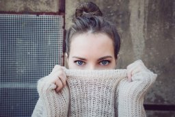 A woman in a light pink knitted jumper pulls it up while looking into the camera.