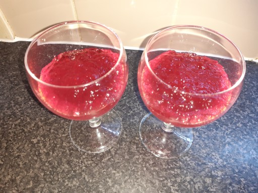 Two wine glasses containing mashed raspberry jelly.