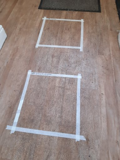 Dirty oak coloured wooden floor with two squares taped out with white masking tape, ready to test two different mop brands.