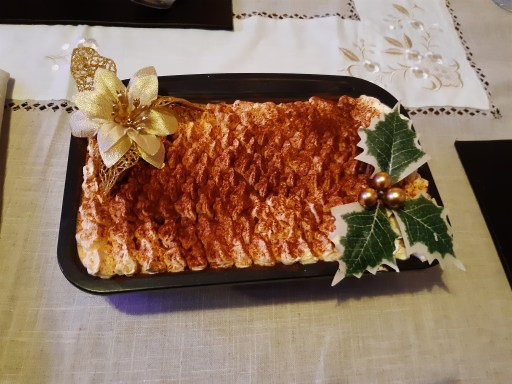A tiramisu with a goild poisettia decoration and holly with gold beads. It sits pm a white, gream and gold tablecloth which has gold embroidery at the top.