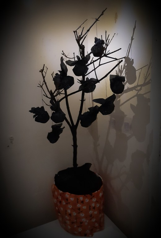 Black Bat Bites hanging on a bkack mini tree in a wrapped plant container. Moody lighting illumunates only the tree.