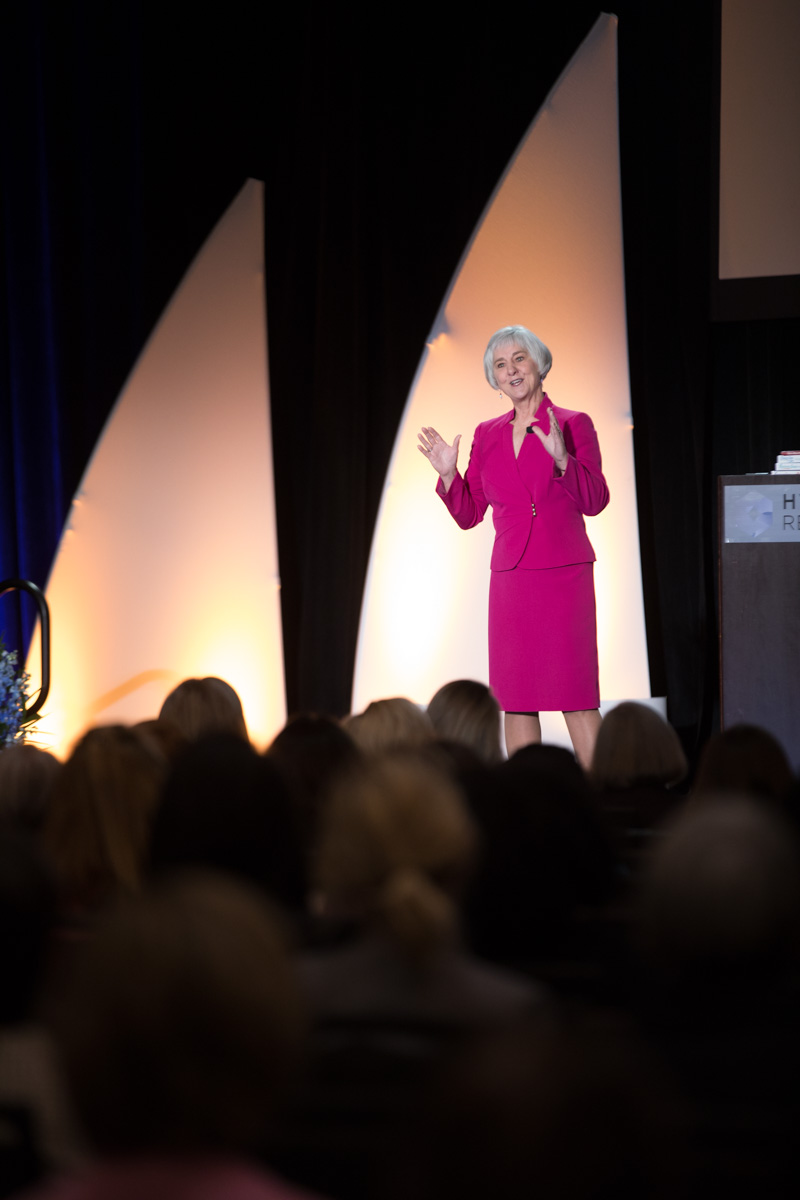 general session speaker, photographer captures speaker on stage at conference for pediatric nurses, pink suit, women addressing audience, full house at conference, Hyatt regency conference, speaker in pink suit