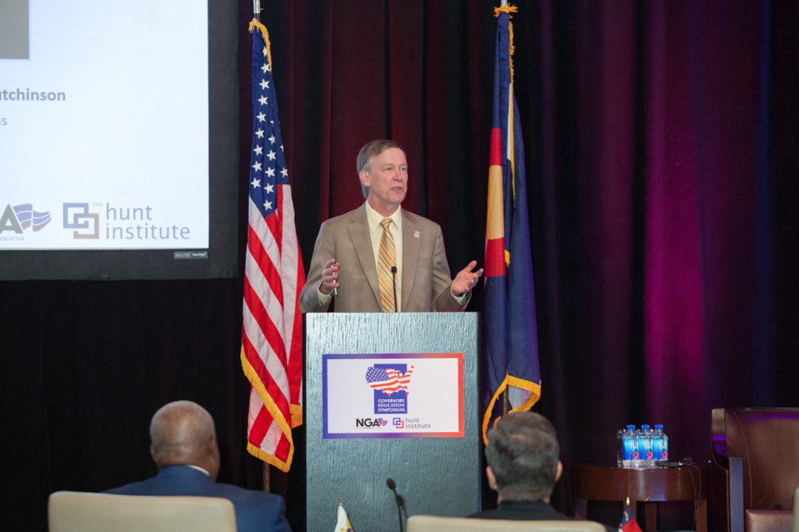 speaker on stage, governor hickenlooper, hunt institute, symposium, speaker with flags in background, speaker addresses audiences, American flag, Colorado flag, event photographer, symposium photographer Denver, four seasons ballroom, meeting photographer Denver,