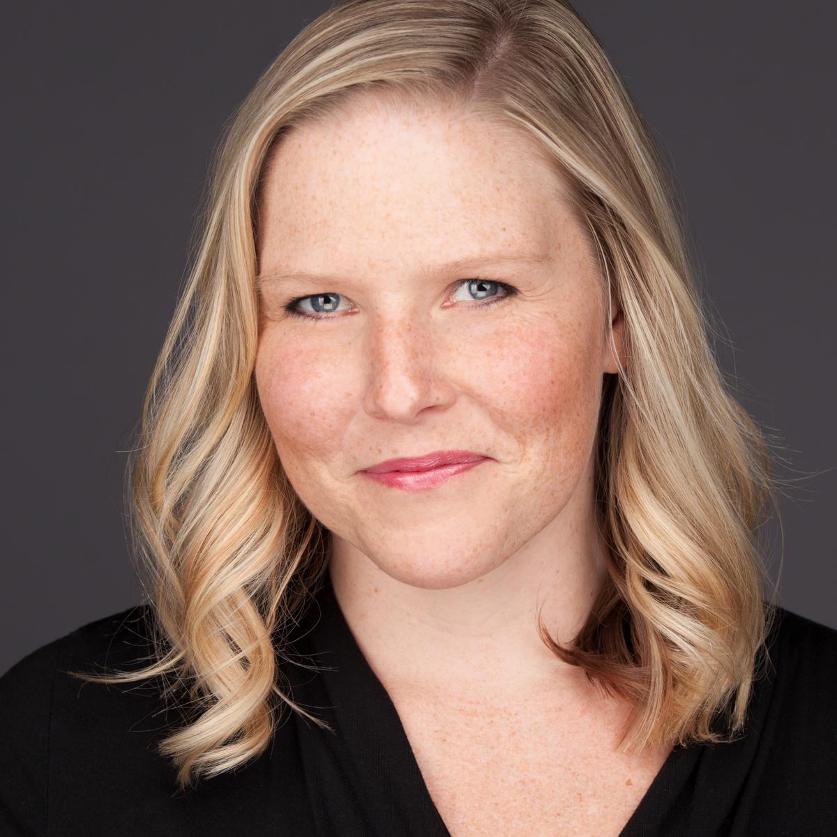 headshot of SLC UT based headshot photographer Laura Kinser, dark background with confident and approachable smile