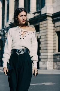 A stylist woman dressed in white sweater and black shirt in Paris