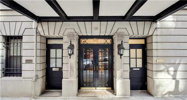 photo of the front door entrance to the building in NYC which is the birthplace of Kirated Communications also known as Kirated.co. The building is located at Sixteen East Ninety Eighth Street, in Carnegie Hill neighborhood in New York City. The building was built in 1925 and has a traditional limestone facade with art deco lines and is very symetrical in this photo.