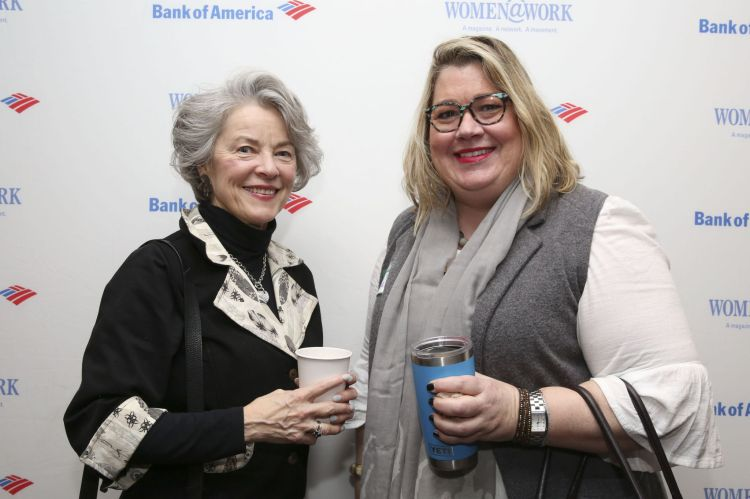 Photo of Ninal Lockwood and Kirsten Voege in front of the logo'd step and repeat. This photo was taken while attending the Women at Work (Women@work) networking event in February at the Hearst Times Union building located off of Wolf Road in Albany NY.