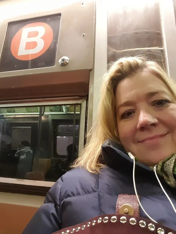 Taking the B train to work in midtown West., listening to a top Podcast