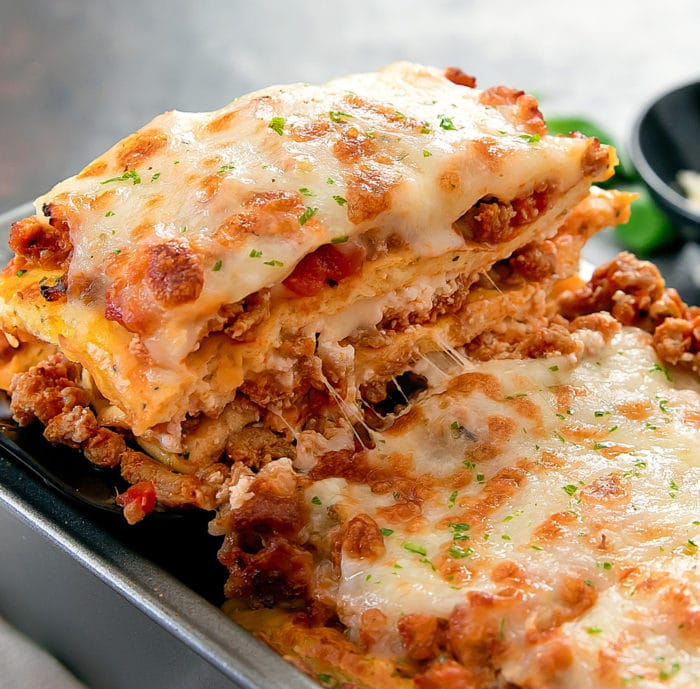 close-up photo of a slice of lasagna being lifted from a pan